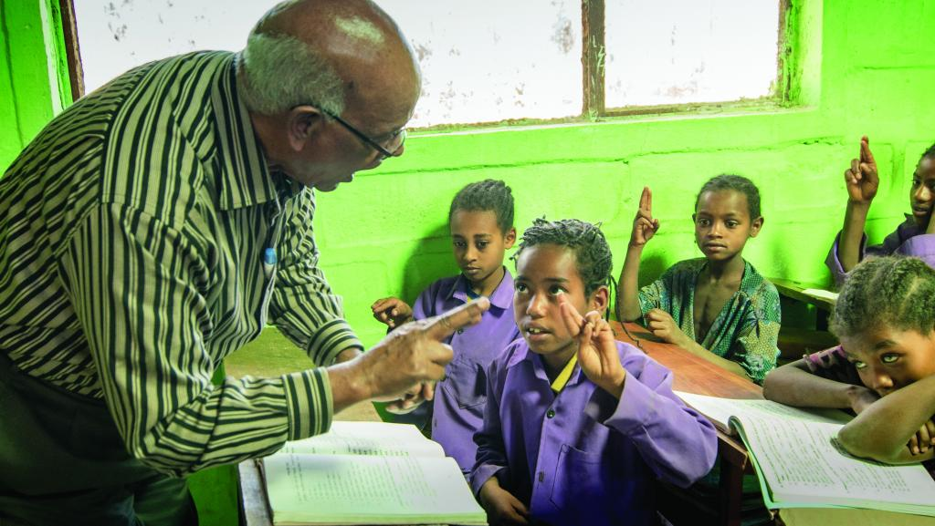 Behailu assisting a deaf student.